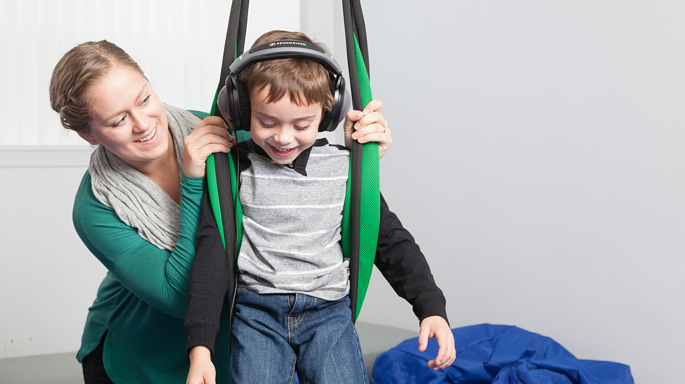 Occupational Therapy, child exercising in flexible gym with therapist, PHOTO